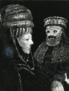 Photograph of actors Priscilla Smith and Jamil Zakkai in full costume and masks during the production of Agamemnon, from the William Harris Papers at Marymount Manhattan College