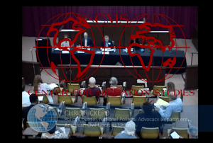 Image shows a view from above of a table with a panel of speakers and a seated audience. Watermarked with Center for Migration Studies logo.