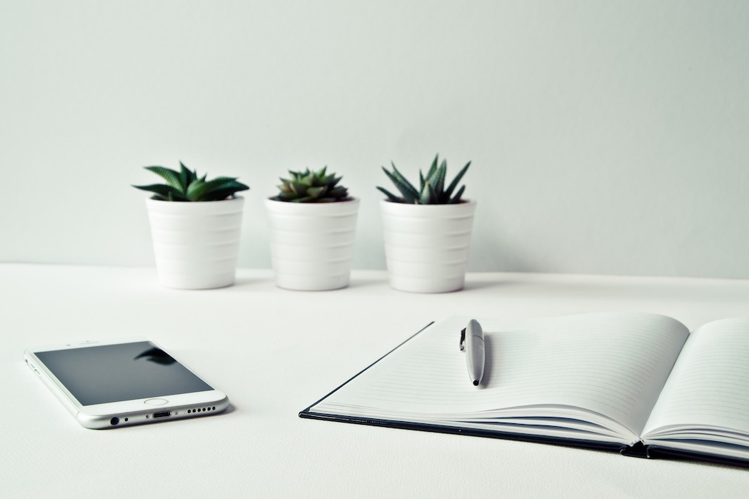 White desk with 3 white plant pots, note pad and pen and a phone