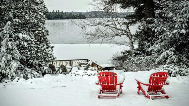 Pair of wooden adirondack chairs in the snow in front of the frozen Lake George