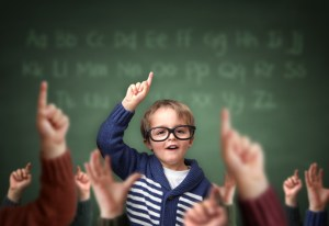 School child with hand raised in the classroom in front of a blackboard with other children concept for teacher's pet, standing out from the crowdand, genius or excelling in education