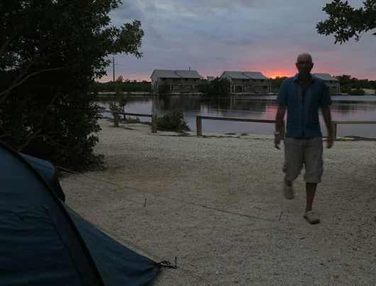 Mann läuft im Abendlicht auf Zelt zu