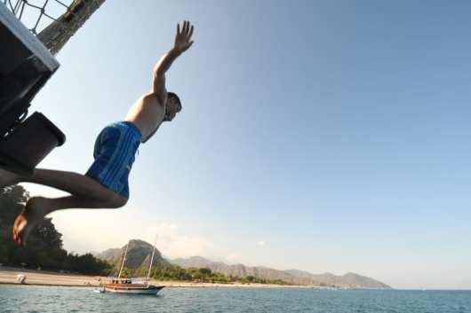 Junge springt von Boot ins Meer