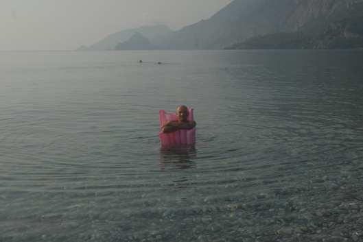 Mann auf Luftmatratze im Meer, dahinter Berge