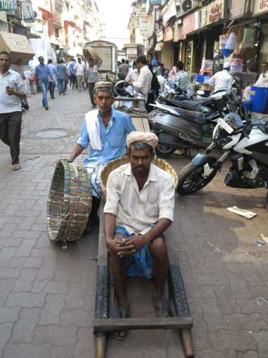 Kulis warten im Marktviertel von Mumbai auf Arbeit