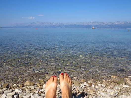 Füße mit lackierten Nägeln vor glasklarem Wasser