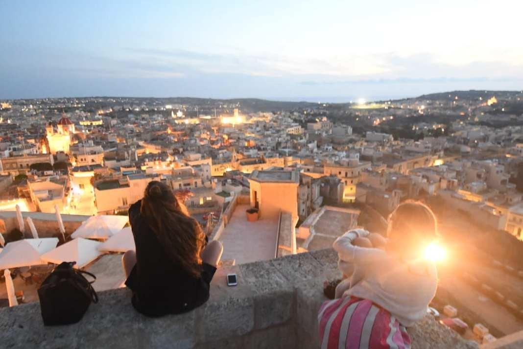 Mädchen blicken im Abendlicht über eine Stadt hinweg