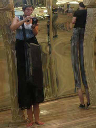 Frau steht in einem Spiegelkabinett