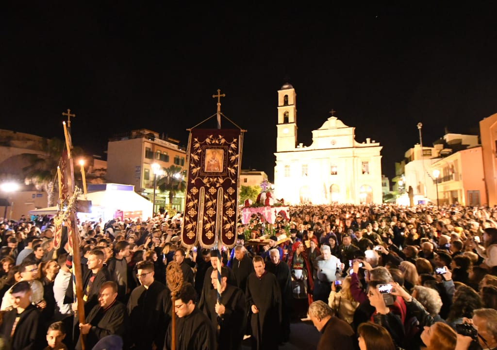 Menschenmassen bei der Karfreitagsprozession vor erleuchteter Kirche auf Kreta