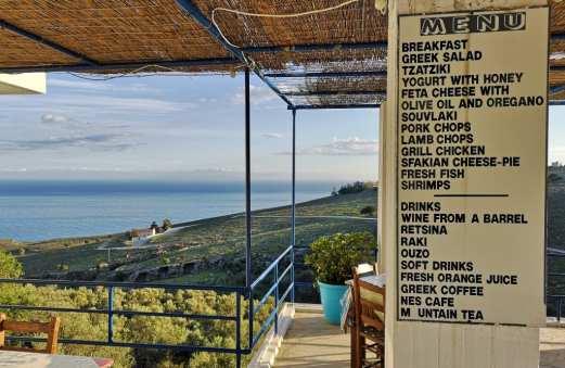 Terasse einer Taverne auf Kreta mit dem Meer dahinter