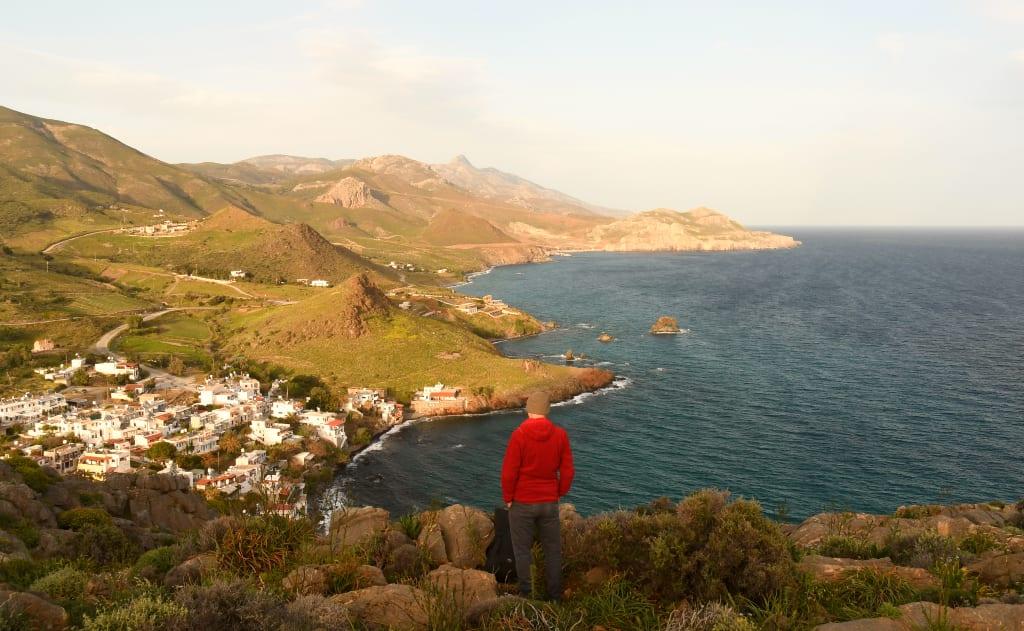 Mann mit rotem Kapuzenpulli blickt über die Bucht von Léntas auf Kreta