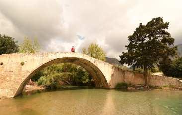 Frau steht auf antiker Brücke auf Kreta