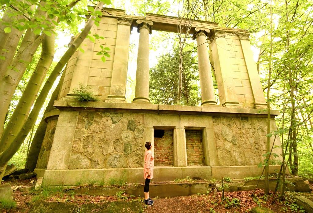 Frau vor Ruine im Wald