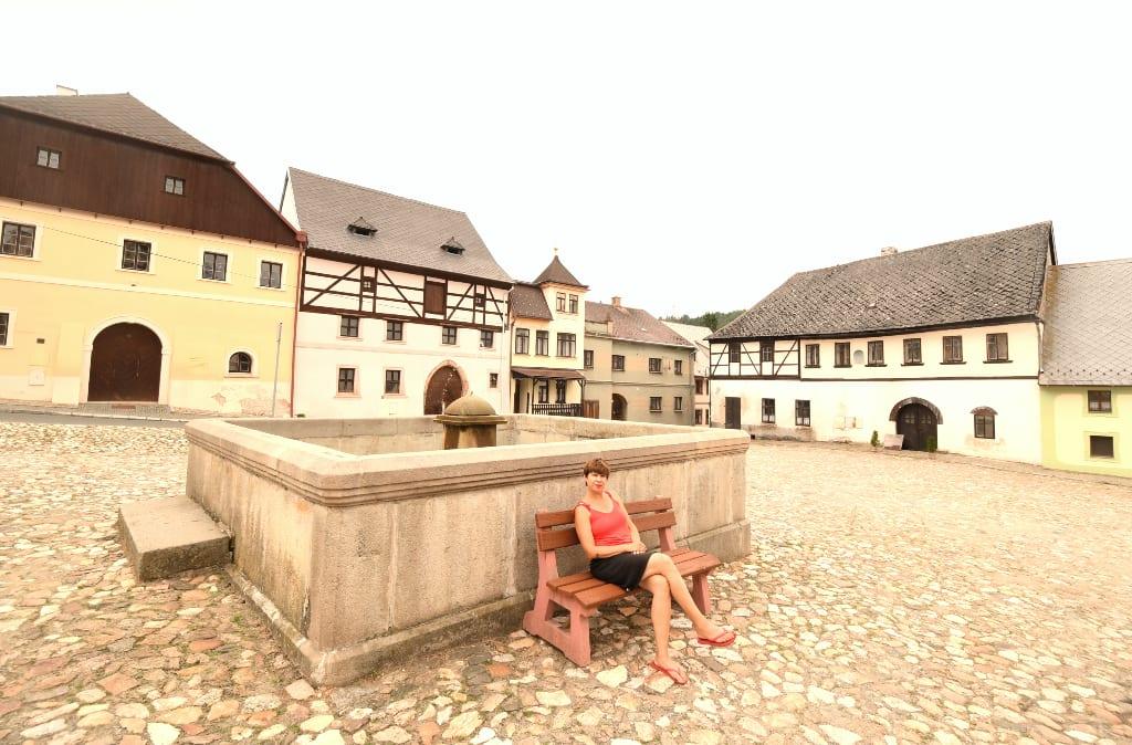Frau sitzt vor einem Brunnen am Dorfplatz in Utery in Westböhmen