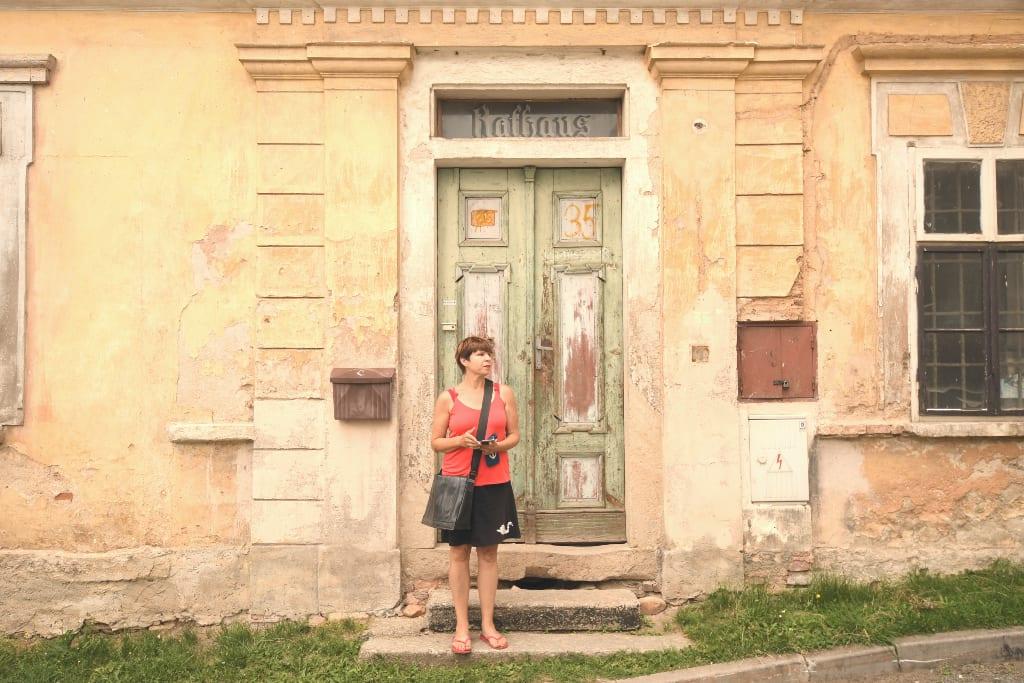"""Frau steht vor einem verwitterten Gebäude mit der Aufschrift """"Rathaus"""" in Utery"""