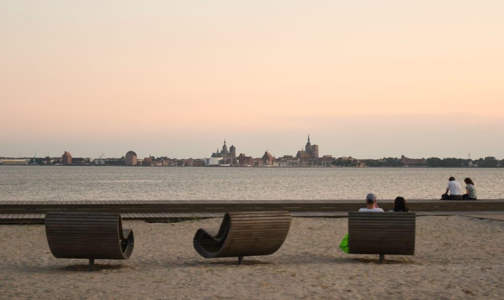 Strand mit Bänken, im Hintergrund das Meer und die Stadt Stralsund