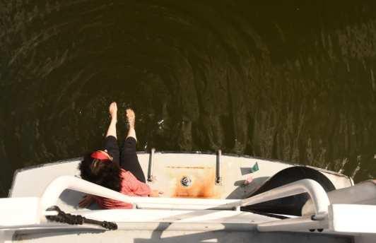 Frau sitzt auf Badeplattform eines Boots