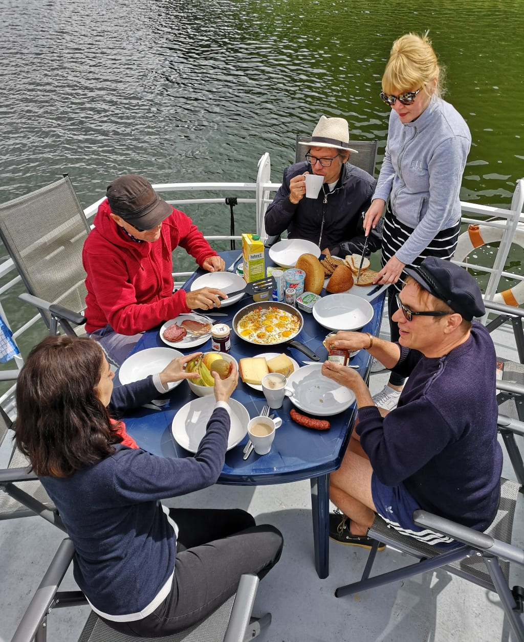 Menschen frühstücken auf Deck eines Bootes