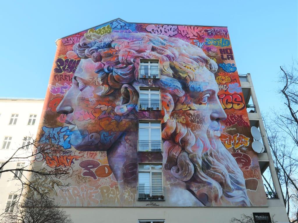 Riesiges Mural mit zwei Gesichtern an Häuserwand