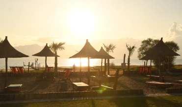 Sonnenschirme an einem Strand bei Sonnenuntergang