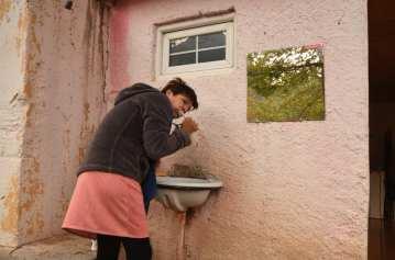 Frau putzt Zähne an einem Open-Air-Waschbecken