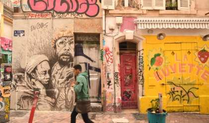 Mann läuft an Wand mit bunter Street Art vorbei