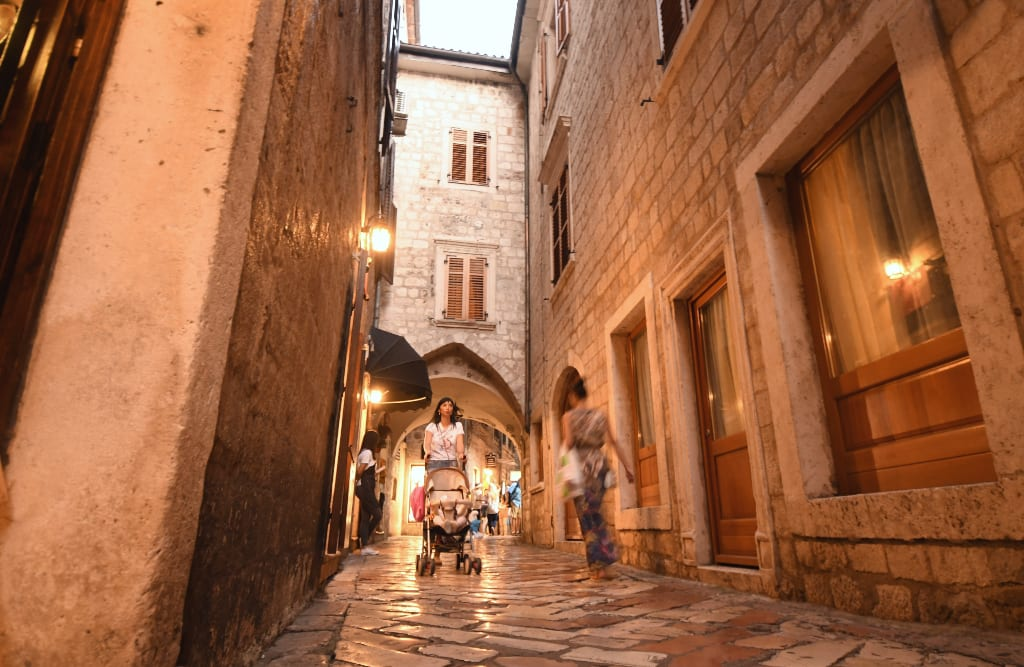 Frau mit Kinderwagen läuft am Abend durch eine Altstadt