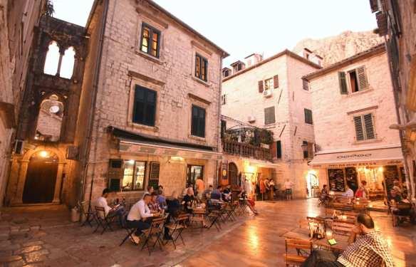 Kleiner Platz mit Restauranttischen im Abendlicht