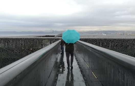 Mann mit türkisfarbenem Schirm