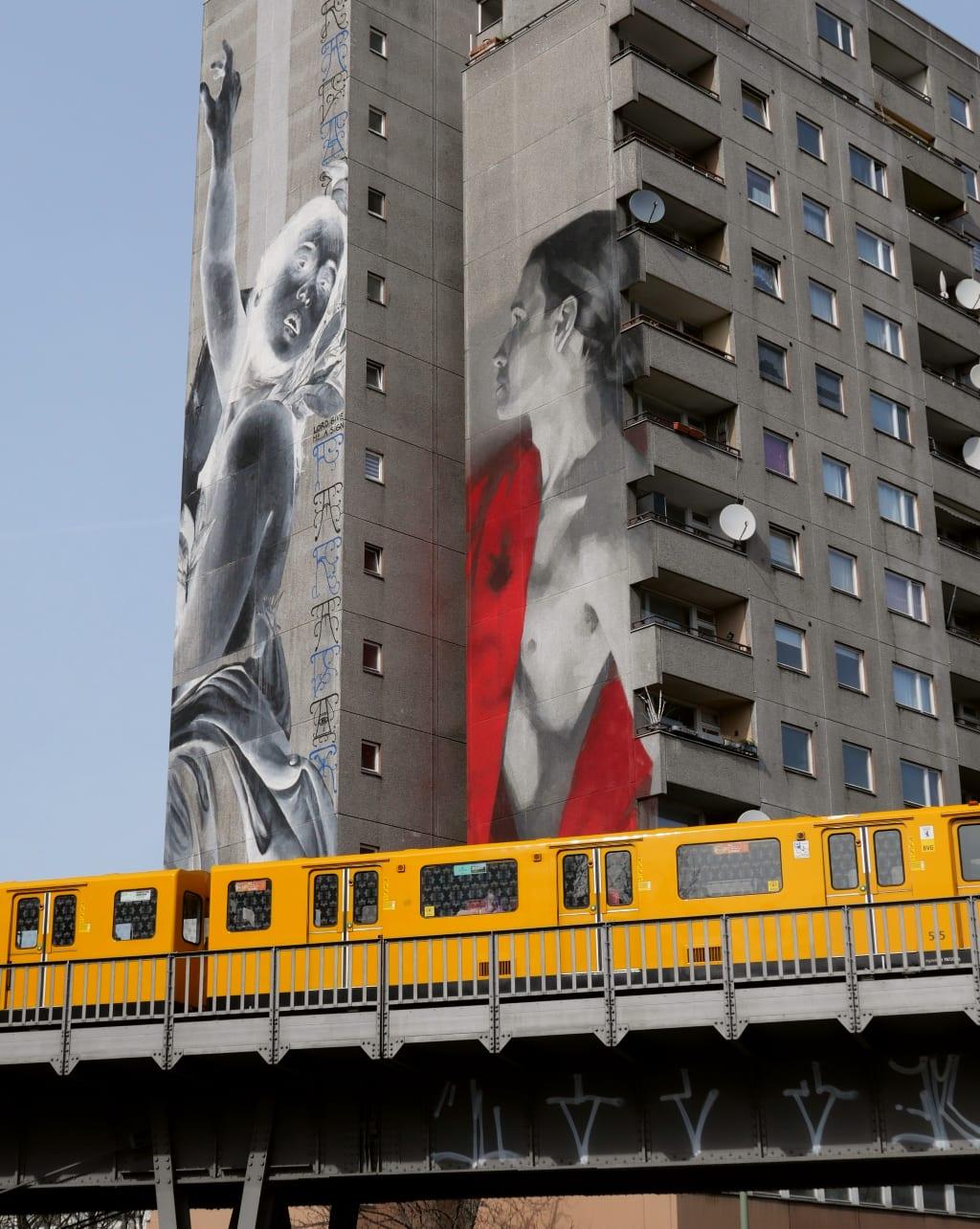 Mural an Wohnblock, davor fährt die Hochbahn