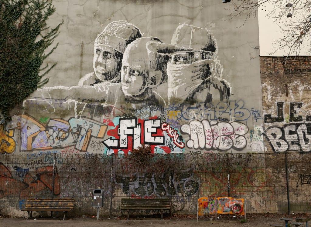 Schwarz-weißes Wandgemälde mit drei Personen an Häuserwand
