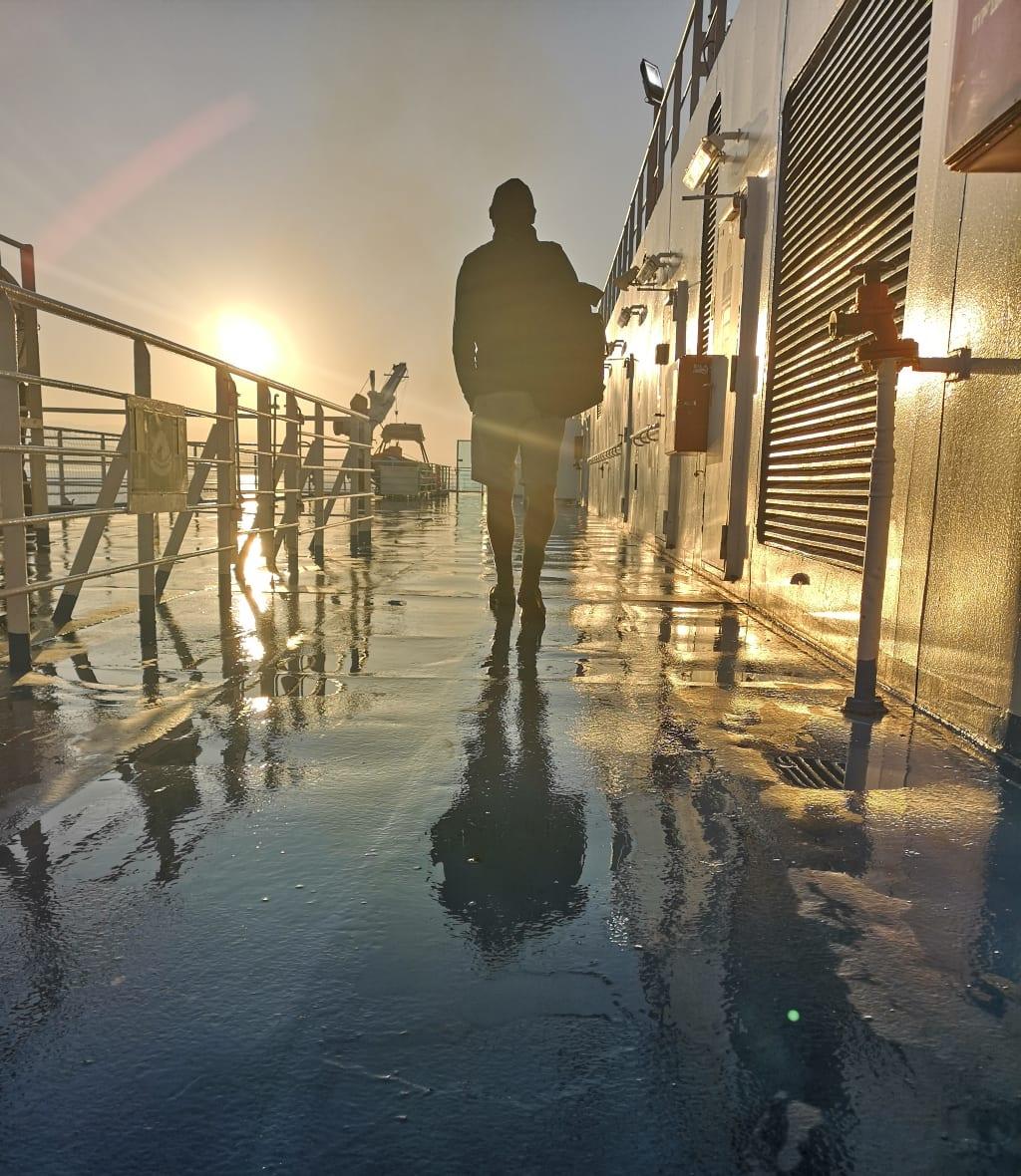 Mann läuft im Sonnenaufgang auf Schiffsdeck