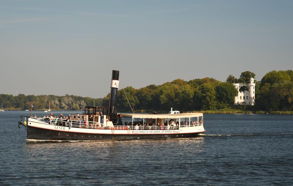 Dampfschiff vor einer Insel mit weißem Schloss
