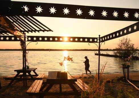 Person läuft im Sonnenuntergang über einem Strand
