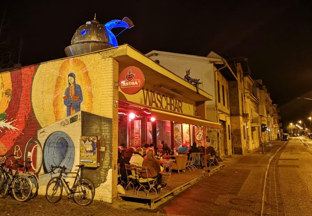 Beleuchtete Bar mit Leuten auf der Terrasse