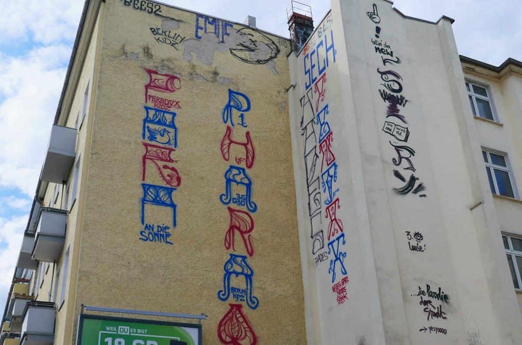 Schriftsäulen an einer Häuserwand