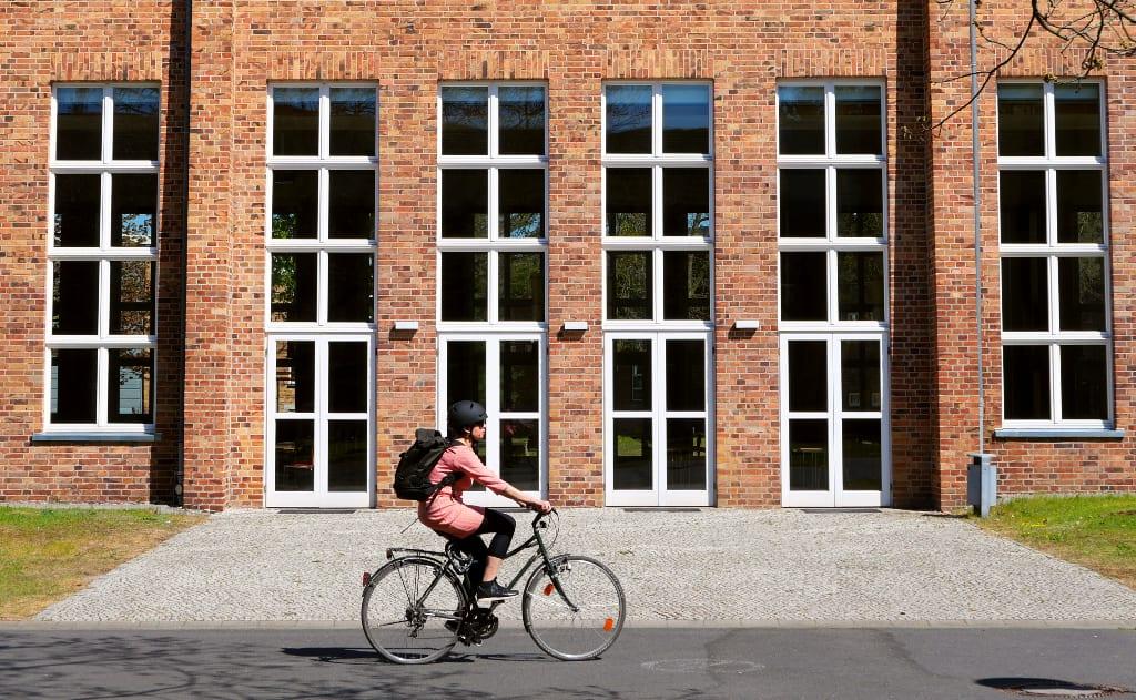 Frau radelt vor Backsteingebäude mit großen Fenstern