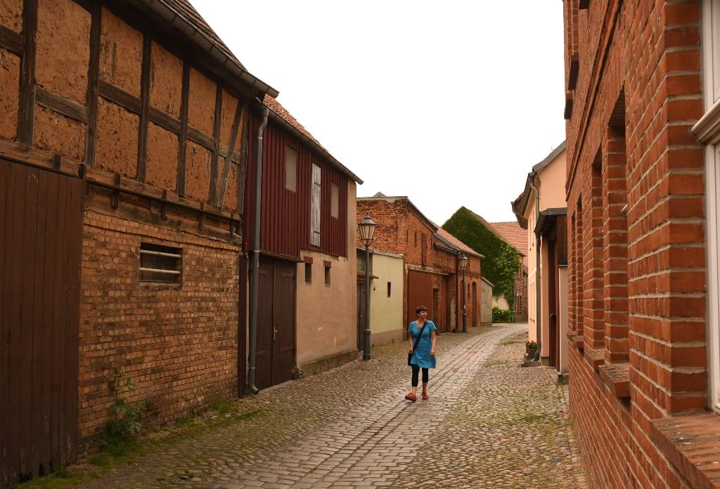 Frau läuft durch stille Straße mit Backsteingebäuden
