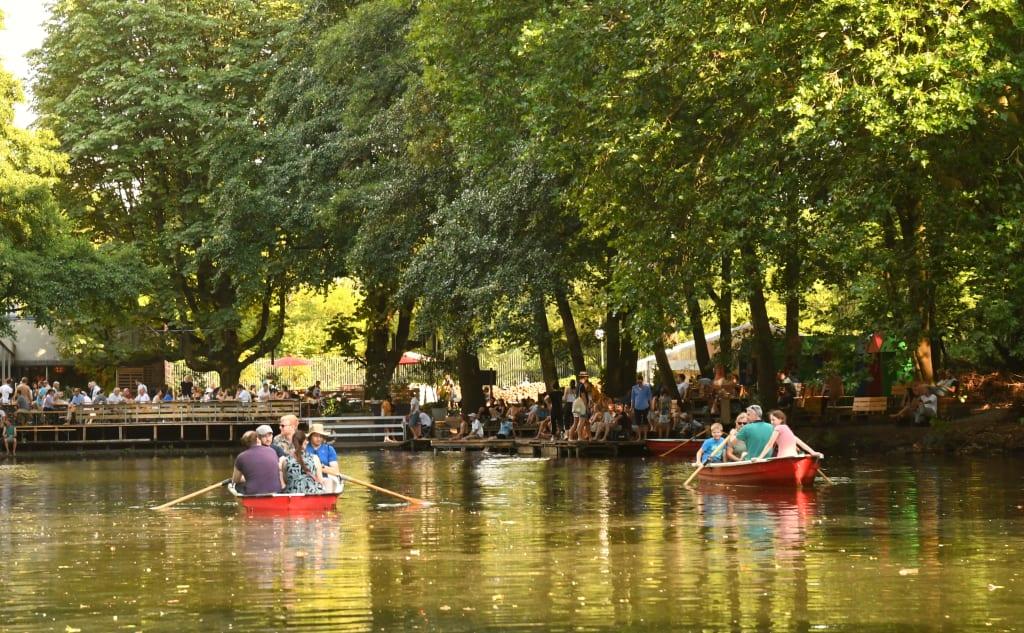Ruderboote in einem See, dahinter Biergarten
