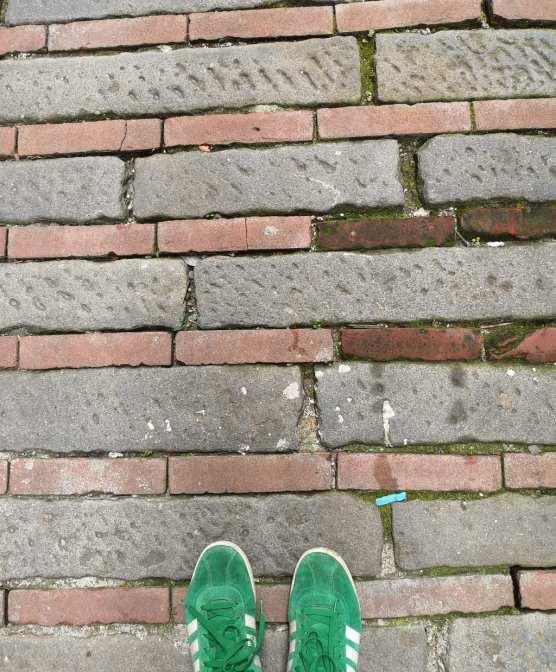 Straßenpflaster mit grünen Sneakers