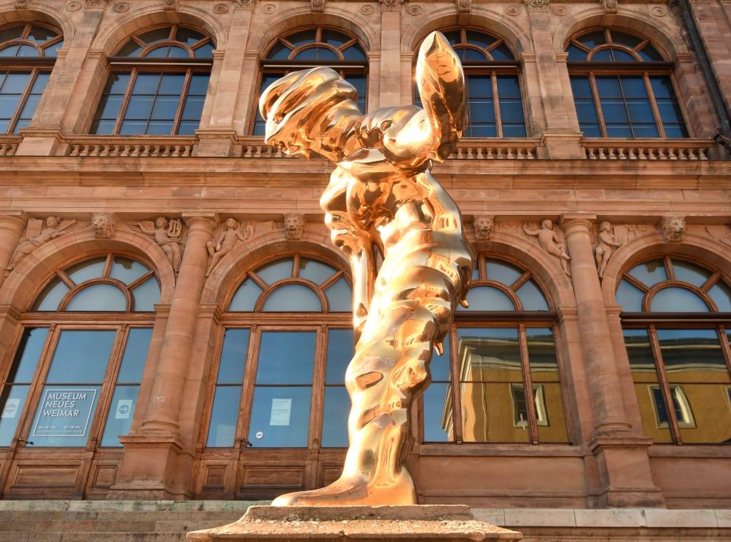 Gläzende Statue vor historischem Gebäude