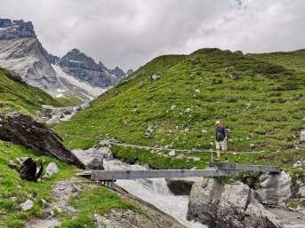 Mann läuft über eine Brücke in den Bergen