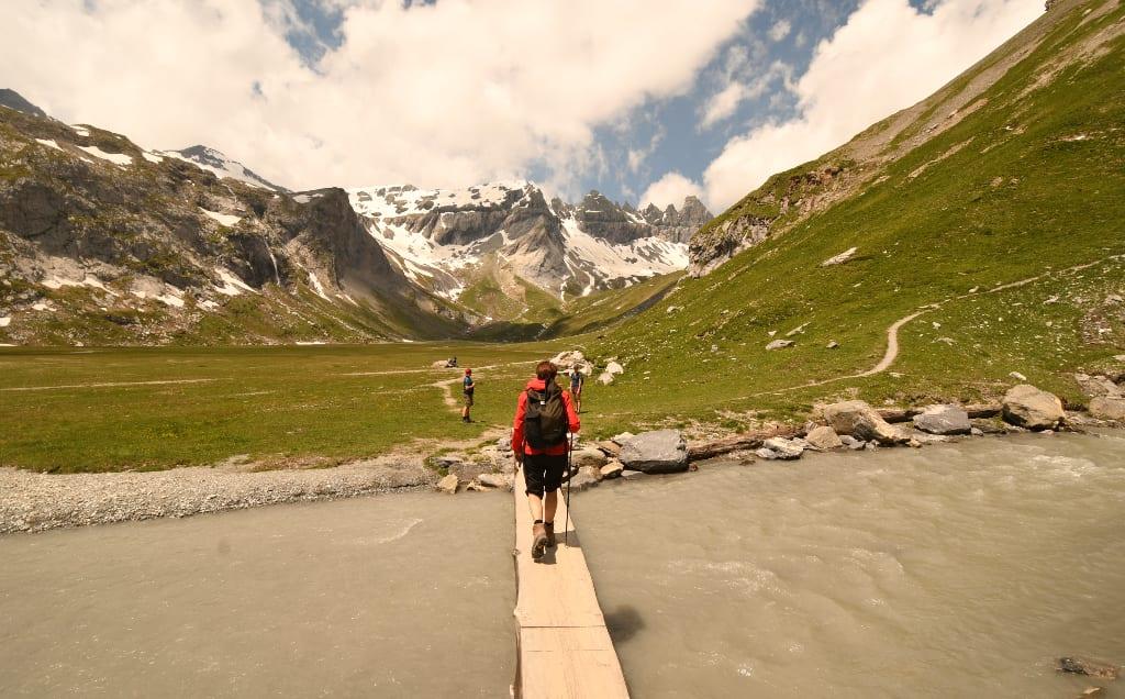 Frau läuft über Gebirgsbach, dahinter schneebedeckte Berge