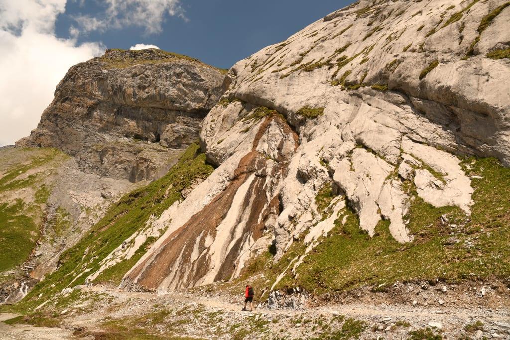 Frau läuft entlang einer Felswand