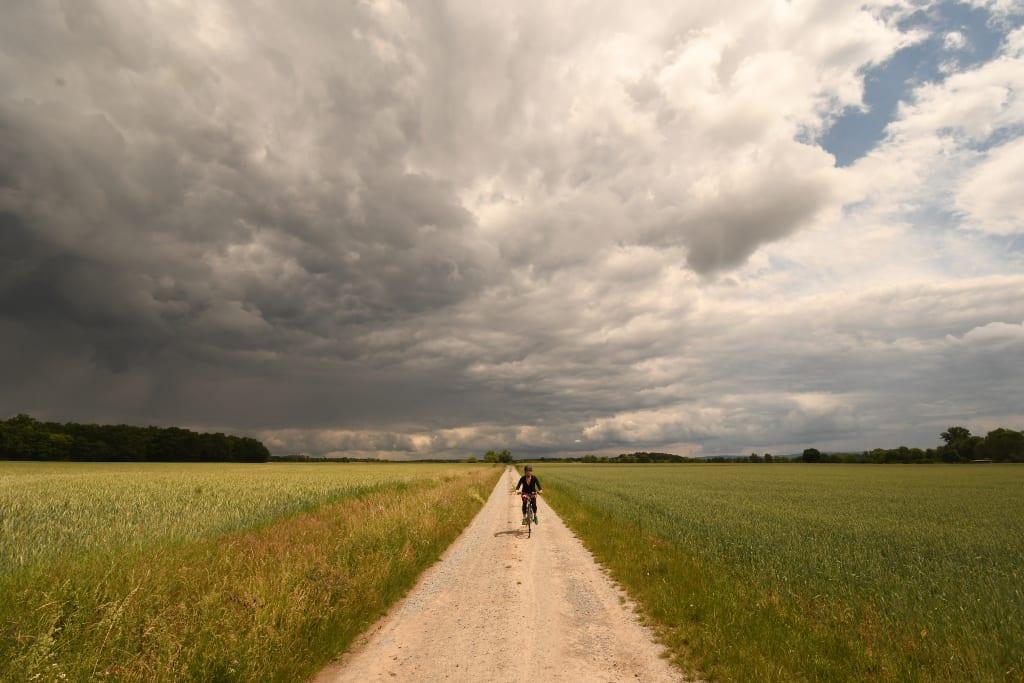 Gewitterstimmunf und Radfahrer auf Feldweg