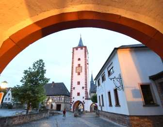 Torbogen, dahinter Turm einer Altstadt