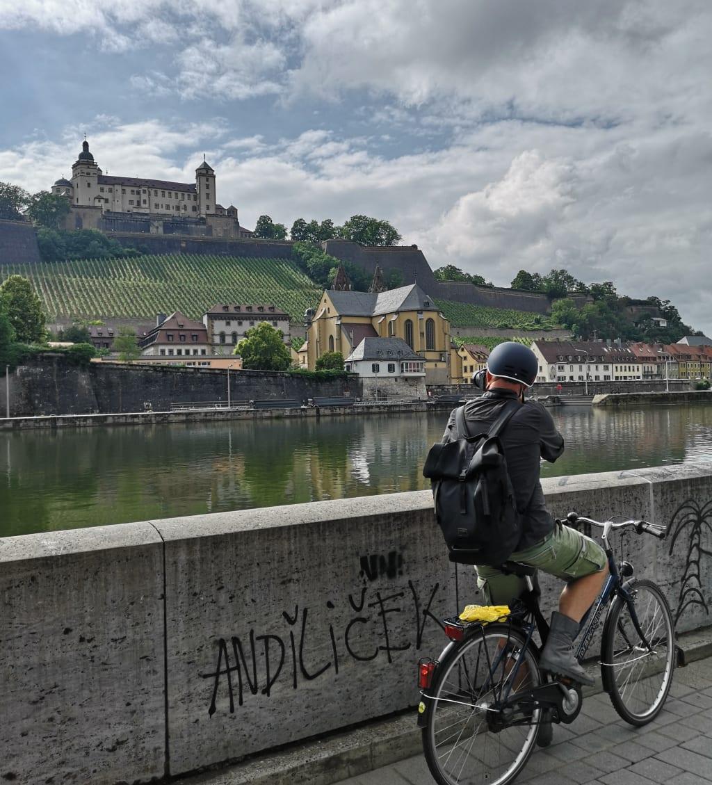Radfahrer blickt auf eine Burg über einem Fluss