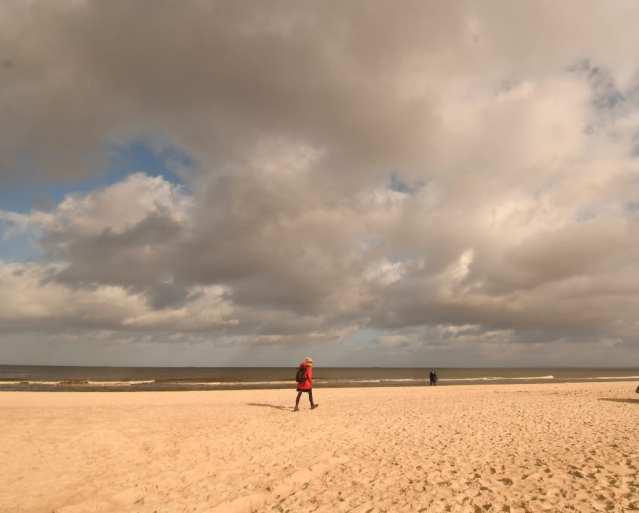 Frau mit rotem Anorak geht einen Strand entlang