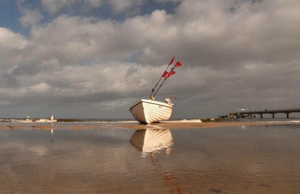 Boot spiegelt sich im Wasser eines Strandes