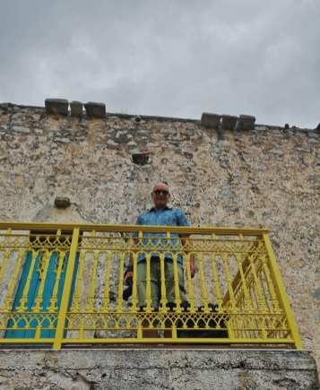 Mann mit blauem Shirt steht auf gelbem Balkon